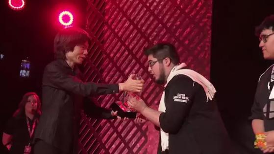 ZeRo recebe o prêmio do Smash Bros. Invitational de 2018 de Masahiro Sakurai | Foto: Reprodução - Millenium